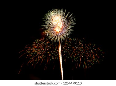 Green and yellow round firework with dazzling colorful small light around tail on black background.