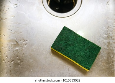 Green and yellow scrubing sponge lying in scratch and wet sink with garage disposal