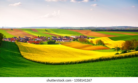 Green and yellow spring fields panorama. Spring meadows. Rural scene. Lower Austria spring colza fields. Village on a hills near Poysdorf