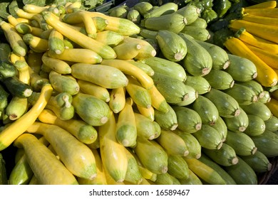 Green and yellow squash vegetables stacked at a market. Horizontally framed photo.