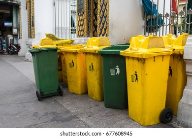 Green and yellow trash cans are on the sidewalk to keep dumpsters.