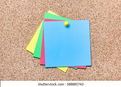 Green, yellow,red and blue notes pined to cork board. Empty reminder cards.