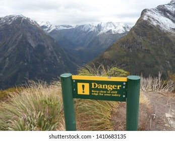 a green and yelow warning sign alerts to the danger of the cliff edge with snow topped mountains in the background while tramping The Milford Track in New Zealand
