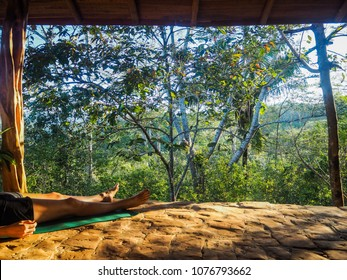 green yoga mat laying outdoors with view to a green sunny jungle