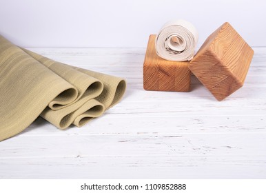 Green yoga mat, two wooden blocks and white belt on white wooden  background with copy space. Yoga practice, relaxation and meditation concept