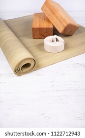 Green yoga mat, two wooden blocks and white belt on white wooden  background. Yoga practice, relaxation and meditation concept.