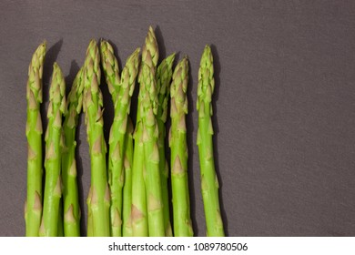 Green young asparagus on the stone board. Top view.