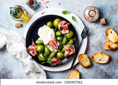 Green zebra tomatoes and sliced burrata cheese salad with fresh arugula, prosciutto or jamon, olives and toasted bread. Overhead view