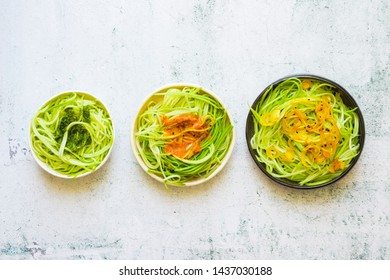 Green zucchini spaghetti or pasta with sauce. Vegan, vegetarian healthy food. White background table.