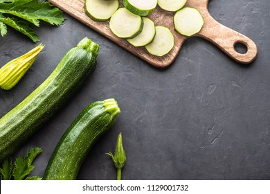 Green zucchini (zucchetti, courgettes) on a black background. Top view.