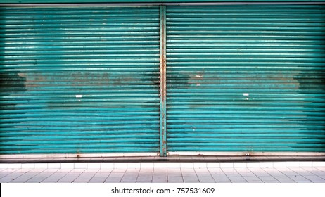 A greenblank metal shutter door, with a copy space for text, on a front modern commercial shop. Shop closed theme.