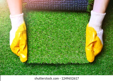 Greenering with an artificial grass background. Landscape designer holds a roll of an artificial turf in his hands. Image with a copy space.
