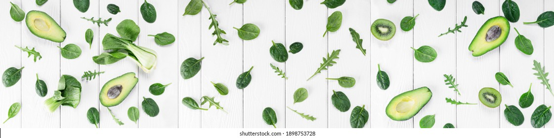 Greenery trendy 2017 color composition, top view of baby spinach and arugula leaves on white wooden background. Long banner