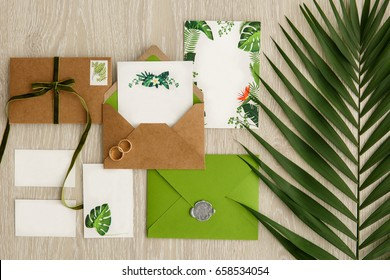 Greenery wedding. Composition of wedding invitations, cards, letters and rings for bride and groom. Copy space for your design