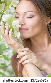 Green-eyed long-haired model in a white T-shirt posing in the jasmine bush. A girl with perfect skin and a smile. Beauty care