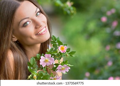 Green-eyed model posing on a green background with a branch of wild rose. A girl with perfect skin and a smile. Beauty care