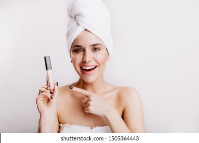 Green-eyed young girl in white towel with smile points to concealer hiding all imperfections of skin