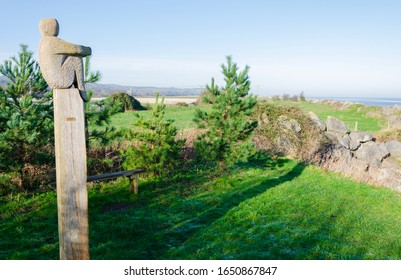 Greenfield, Flintshire, UK: Feb 6, 2020: The Lookout is a carved wood sculpture by Mike Owens. The sculpture faces the River Dee estuary on the North Wales Coastal Path.