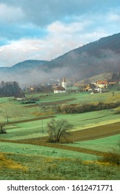 Greenfield and town in Slovenija surrounded by mountains