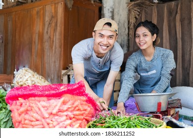 greengrocer couple smiles as they put together a vegetable display at a vegetable stall at a traditional market