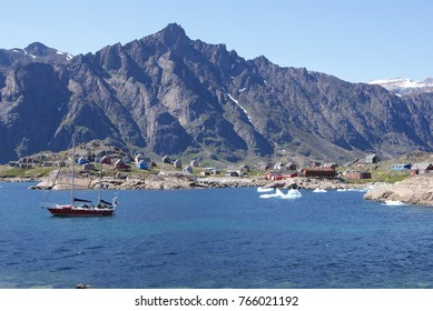 Greenland,: bay with an inuit village and a sailing boat