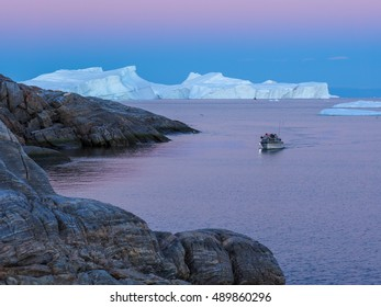 Greenland. Centuries-old thicknesses of glaciers. Motorboat in front of Icebergs Research of a phenomenon of global warming