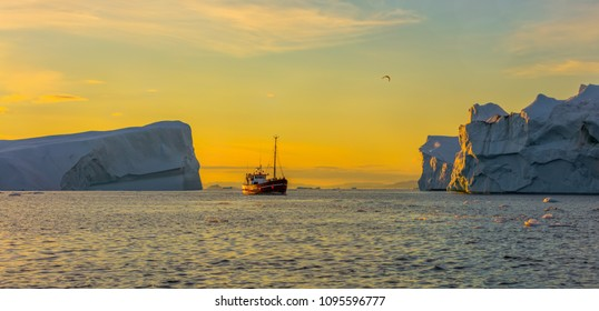 Greenland, Disko Bay. Tourists take pictures of the iceberg. Source of icebergs is by the Jakobshavn glacier. This is a consequence of the phenomenon of global warming and catastrophic thawing of ice