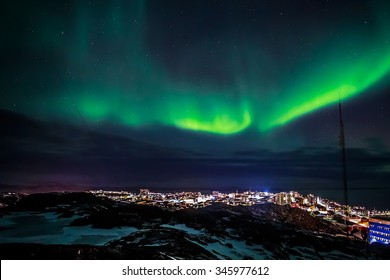 Greenlandic Northern lights and starlight sky over highlighted Nuuk city view from top of rocky hill, Greenland