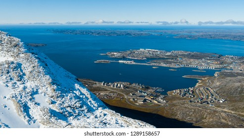 Greenlands capital Nuuk - largest city in Greenland aerial view. Drone image of Nuuk from air, aka Godthaab seen from Mountain Sermitsiaq also showing Nuup Kangerlua fjord.