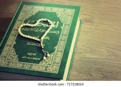 Greens Holy Quran Book With Rosary on a brown wooden background. Prayer Concept. toned