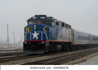 Greensboro, NC / USA - February 10, 2018: Amtrak 74 Piedmont train passing by in Greensboro North Carolina pulling passenger cars on a fog covered day