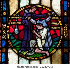 """Greensburg, PA - November 18, 2017: Stained glass window in St. Emma's Monastery depicts St. Benedict receiving a monk's habit from Romanus, as described in the """"Life and Miracles of St. Benedict"""""""