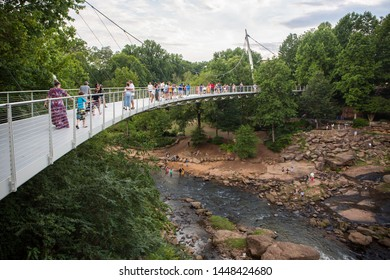 GREENVILLE, SC (USA) - July 5, 2019: Visitors to Falls Park linger on Liberty Bridge overlooking the Reedy River waterfalls.
