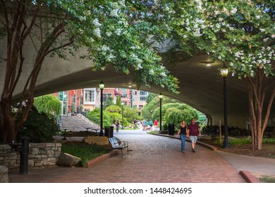 GREENVILLE, SC (USA) - July 5, 2019: A view of the downtown River Walk along the Reedy River as it passes beneath the S. Main Street bridge;