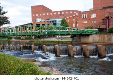 GREENVILLE, SC (USA) - July 5, 2019: A view of the Reedy River and waterfalls along the River Walk with the Eugenia Duke Bridge in the background.