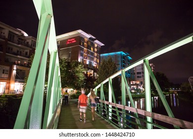 GREENVILLE, SC (USA) - July 5, 2019:  A night-time view from the Eugenia Duke Bridge of the downtown River Walk with the River Place development of hotels, restaurants and shops.