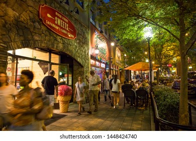 GREENVILLE, SC (USA) - July 5, 2019: Visitors to downtown Greenville create a busy sidewalk scene on a warm summer night.