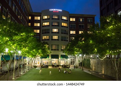 GREENVILLE, SC (USA) - July 5, 2019:  An after-dark view of the downtown Marriott Courtyard hotel with children playing in front.