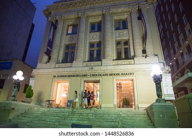 GREENVILLE, SC (USA) - July 5, 2019:  Shoppers visit a bakery and bookstore in a repurposed building on a warm summer night downtown.