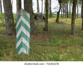 Green-white wooden pillar in the forest. Selective focus.