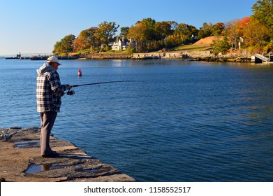 Greenwich, CT, USA October 27, 2013 An adult man casts his line to fish along the Greenwich, Connecticut waterfront in fall