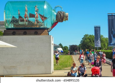 """GREENWICH, LONDON, AUGUST 27, 2016: """"Nelson's Ship In a Bottle"""" by Yinka Shonibare - replica of Nelson's HMS Victory in a bottle at National Maritime Museum with visitors passing by on a summer day."""