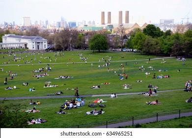 Greenwich, London- July 11,  2015: People are relaxing by having a sunbath on the grass in Greenwich, London, UK