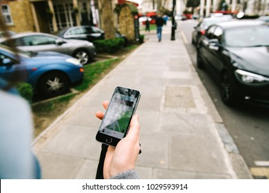 GREENWICH, LONDON, UNITED KINGDOM - MAR 10 2017: Woman order waiting for the UBER taxi cab on British street  - point of view looking at the phone on the street