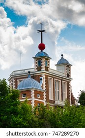 The Greenwich Old Royal Observatory with the red time ball on top of the Octagon Room. Clouds are building in the blue sky.