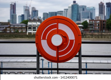 Greenwich, UK-May 25, 2019: view of Canary Wharf skyscrapers from Greenwich pier in South London with lifebuoy in foreground next to River Thames