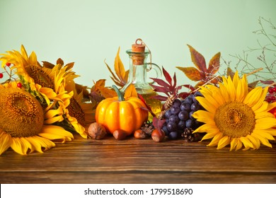 Greeting autumn card with copy space. Composition with pumpkin, autumn leaves, grape, sunflower, candle and berries on the wooden background. Cozy autumn mood concept