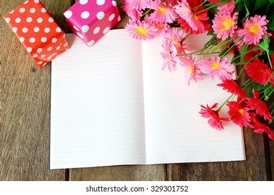 Greeting book and beautiful flower with gift box on wooden background