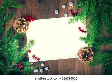 greeting card for the Christmas holidays . Spruce branches , cones and red berries covered with snow . Space for labels on a wooden surface .