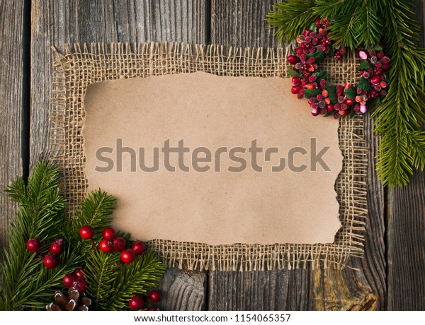 greeting card for the Christmas holidays . Spruce branches , cones and red berries covered with snow . Space for labels on a wooden surface . mocap